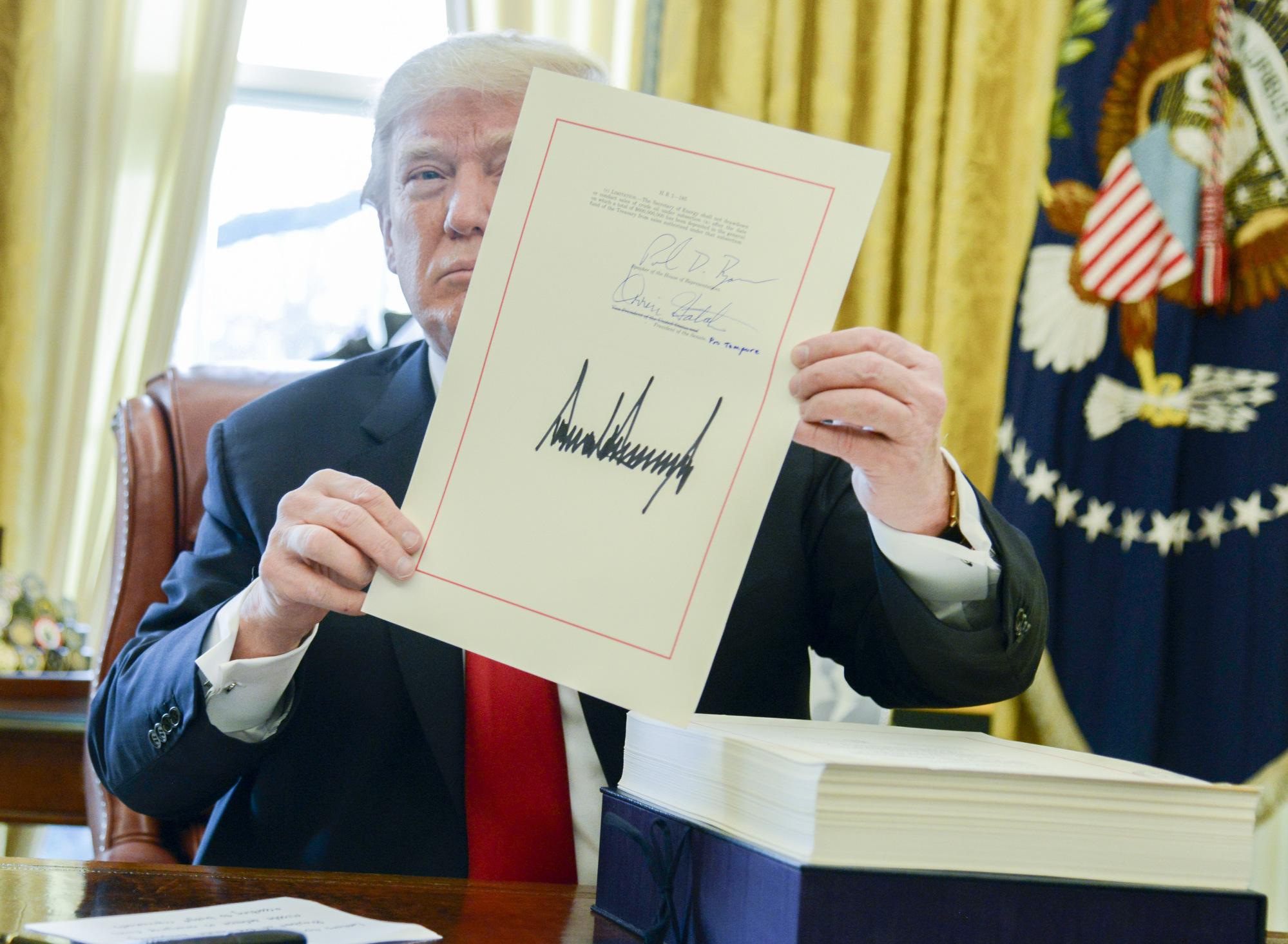 https://assets.sourcemedia.com/0b/29/cd68a633438383de5f0bb76d2097/trump-tax-bill-signature.jpg