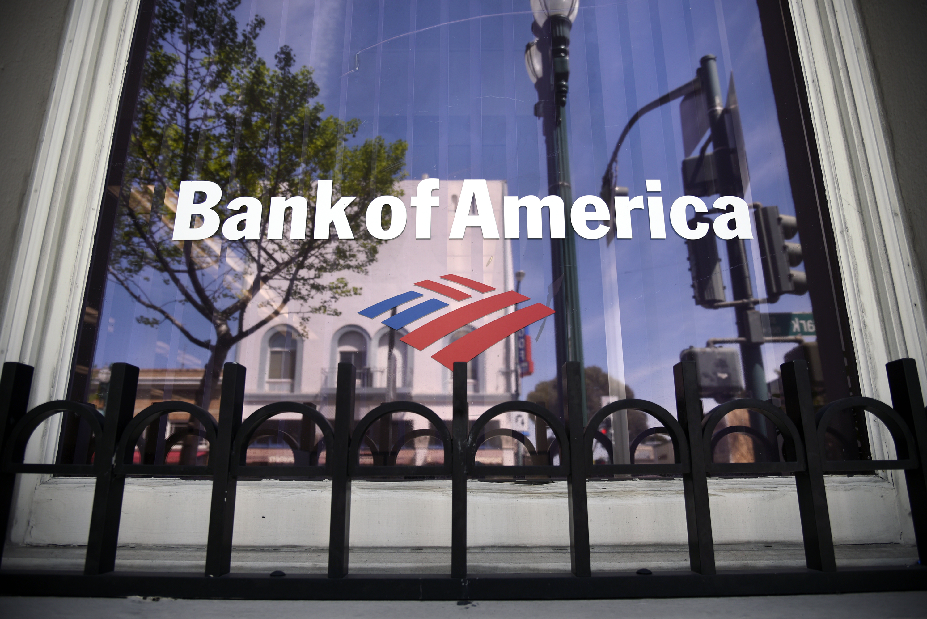 buildings are reflected in the window of a bank of america corp branch in Alameda California